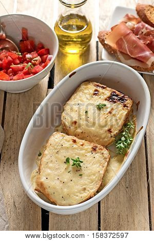 French sandwiches Croque-Monsieur with bechamel sauce tomato salad and prosciutto ham