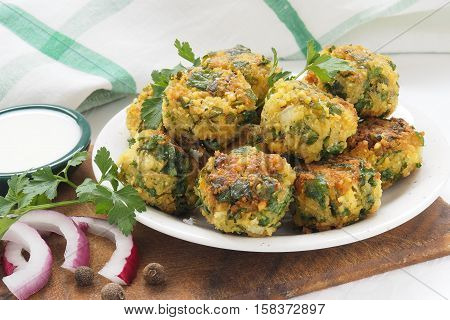 Chickpeas falafel with sauce and ingredients on white plate