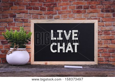 LIVE CHAT word on blackboard with green plant