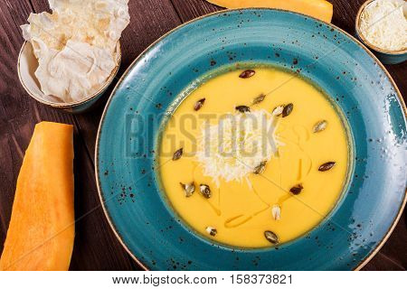 Pumpkin and carrot soup with parmesan cheese pumpkin seeds and bread on dark wooden background. Top view