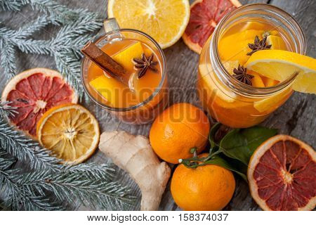 Winter healing ginger drink with lemon honey and oranges. Cinnamon star anise fir twigs tangerines dried grapefruit. Winter christmas background top view. Love for a healthy raw food concept.