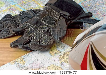 Motorcycle Helmet, Gloves, And Road Maps On A Wooden Table