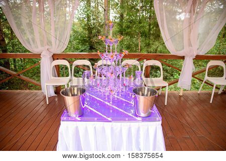 Champagne glasses. Wedding slide champagne for bride and groom outdoors. Colorful wedding glasses with champagne. Catering service. Catering bar for celebration. Beauty of bridal interior for wedding