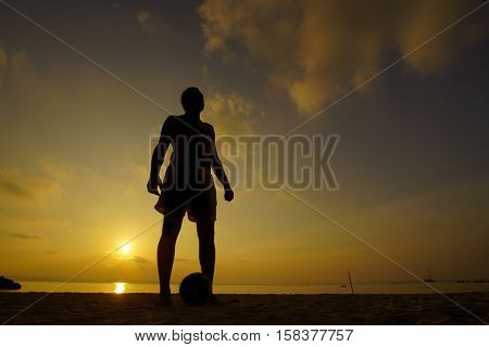 Silhouettes of soccer players during sunset .