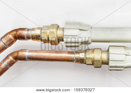 Close view of copper and plastic pipes connect on white background
