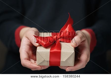 female teen hands show craft paper gift box with red bow, shallow focus