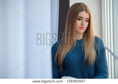 Girl in a blue woolen sweater waiting at the window
