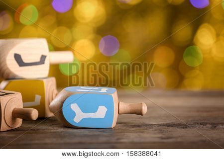 Dreidels for Hanukkah on wooden table against defocused lights, close up
