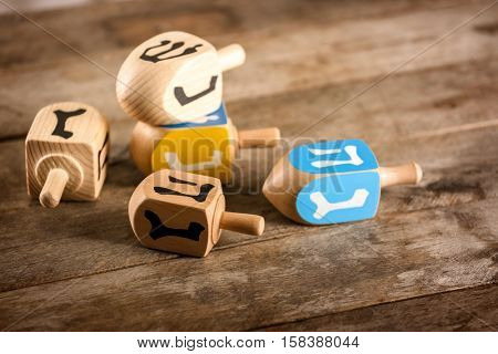 Composition of dreidels for Hanukkah on wooden table