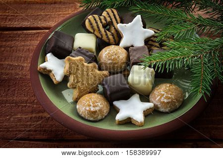 Christmas cookies and fir branches plate full of traditional gingerbread cakes cinnamon stars and pepper nuts on a rustic wooden table selected focus