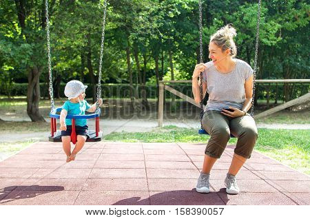 baby mother swing playground looking each other