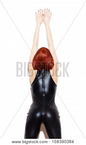 Sexy redhead dominatrix posing at wall isolated on white