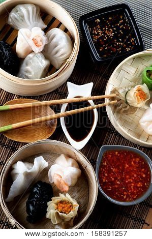 Arrangement of Various Dim Sum in Bamboo Steamed Bowls Black and Red Chili Sauces Soy Sauce and Chopsticks closeup on Straw Mat background. Top View