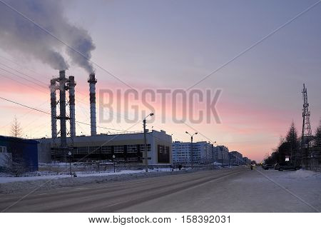 Pipes of the Steamshop or Boiler-house on the city street in the frosty evening. North