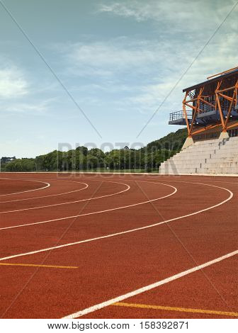 Daytime photograph showing the curve of athletics track with blue sky.