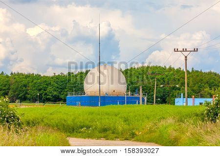 Bio gas plant with green grass and cloudy sky