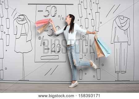 So many clothed. Overjoyed beautiful young woman smiling after having shopping while posing on a grey background.