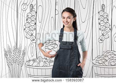 Fresh and tasty. Cheerful young pretty farmer woman standing in barn and holding cabbage while smiling.