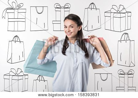 Buy with pleasure. Beautiful young delighted woman holding packages after doing shopping and smiling.