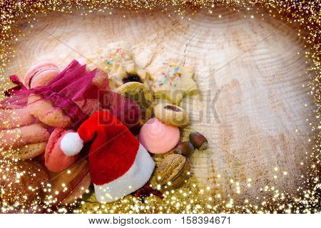 Various Christmas cookies in red sack solated on wood background. Christmas decoration with hat.