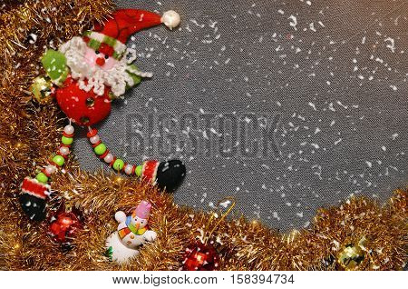 Christmas background for an inscription. On a gray velvety red background Santa Claus and snowman tinsel. Space for text. New Year's background with snow. texture card