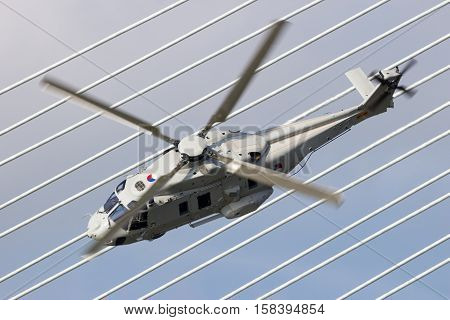 ROTTERDAM NETHERLANDS - SEP 3 2016: Royal Netherlands Navy NH90 helicopter flying past the Erasmus bridge during the World Harbor Days in Rotterdam.
