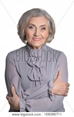 Portrait of confident smiling senior woman in grey blouse isolated on white background