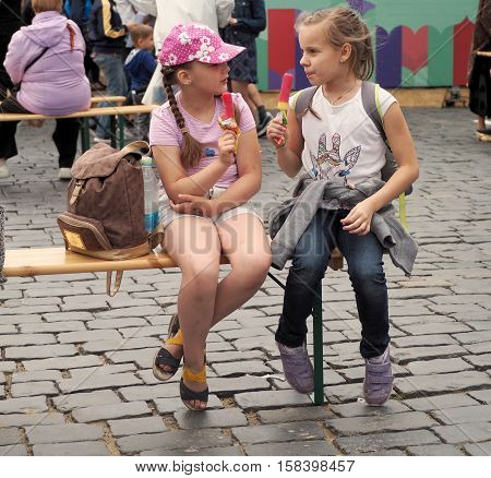 MOSCOW, RUSSIA - June 5, 2016: Two elementary age girls sitting on a bench with ice cream in the square on the book fair. June 5, 2016 in Moscow, Russia