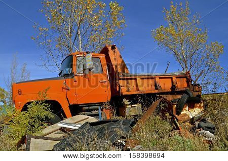 An orange painted county dump and sand truck is left in the junkyard for scrap metal and salvage.
