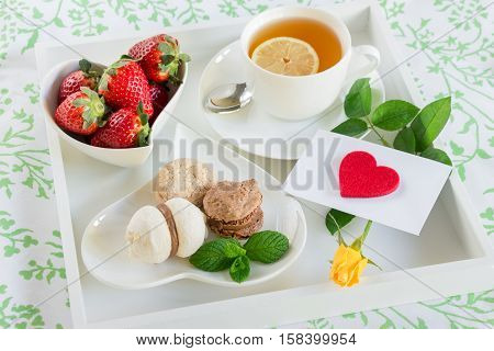 Breakfast in bed of green tea strawberries sweets and red heart yellow rose envelope on a white tray. Romantic breakfast in bed and love letter. Horizontal. DAylight. Close up.