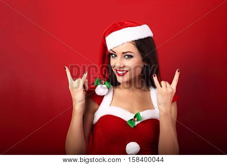 Beautiful Smiling Happy Casual Woman In Santa Clause Costume Showing Rock Sign By Manicured Hands On