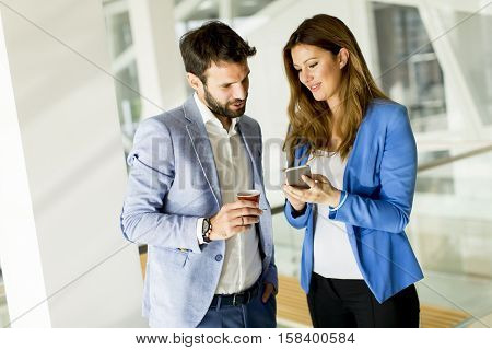 Businesswoman with male colleague discussing looking smart phone and man driking coffee