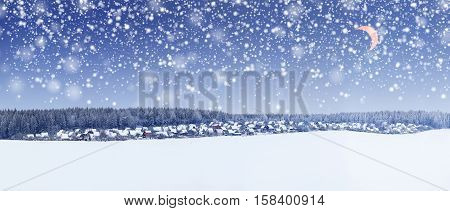 Snowfall in Christmas morning. Young moon in sky. Xmas winter landscape.