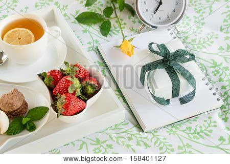 Breakfast in bed of green tea strawberries sweets on a white tray next to a gift box yellow rose alarm clock. Romantic breakfast in bed and gift happy morning concept. Horizontal. Daylight. Close.