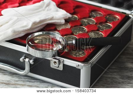Different size collector's coins in the box and magnifying glass on the table