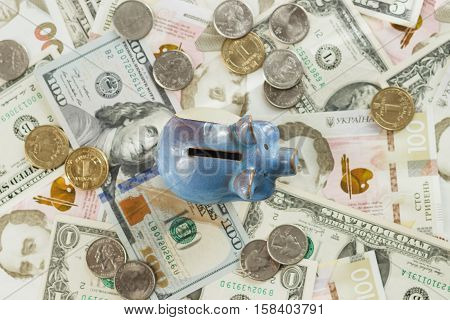 Different collector's coins and banknotes with a piggy bank wooden background
