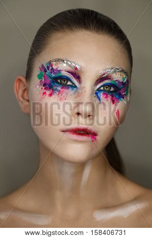 Studio portrait of young beautiful woman with creative colorful brushstroke makeup.