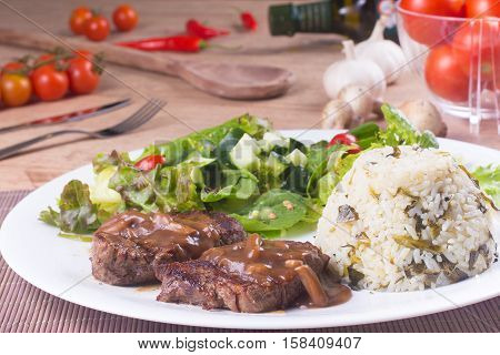 Fillet mignon rice and Fresh and healthy Salad over a wooden table