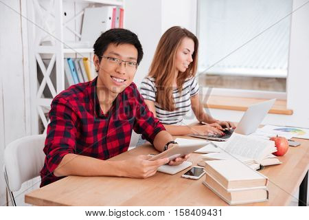 Picture of asian boy wearing glasses and dressed in shirt in a cage and caucasian girl dressed in t-shirt in a strip print working together for project while sitting at classroom.