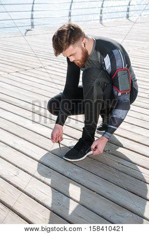 Vertical image of runner preparing near the sea. tying shoelaces