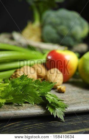 Ingredients for Waldorf salad - celery apples walnuts - fresh and healthy vegetables on granite board.