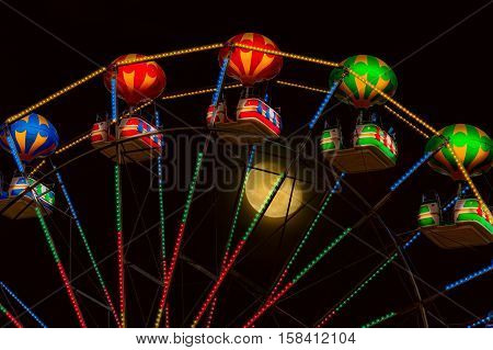 Ferris Wheel at Night against the Moon
