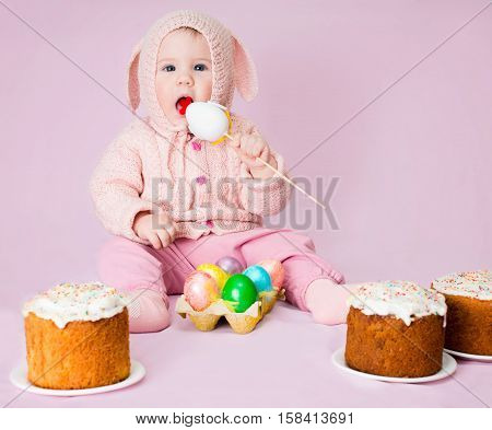 Cute funny baby girl in a costume of Easter bunny rabbit with ears homemade easter cakes and a basket of eggs on pink background. Poster for Easter holiday.