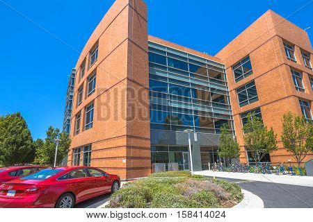 Mountain View, California, United States - August 15, 2016: Google Building 1950 with red car and colored bikes parked. Google is a multinational corporation.