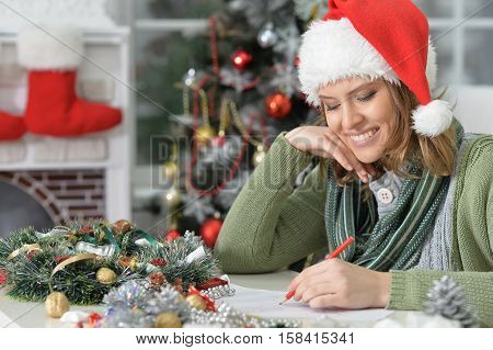 Portrait of beautiful young smiling woman in Santa hat writing letter
