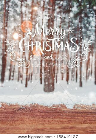 Christmas background with fir trees and blurred background of winter with text Merry Christmas and Happy New Year and wooden table with snow place. Frosty winter landscape in snowy forest