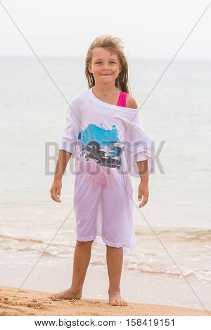 Cheerful Girl Basking On The Beach Wearing A Large T-shirt Parent