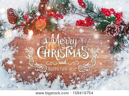 Christmas and New Year typographical on holiday background with Xmas decoration branch of fir tree and snow. Merry Christmas and Happy New Year theme