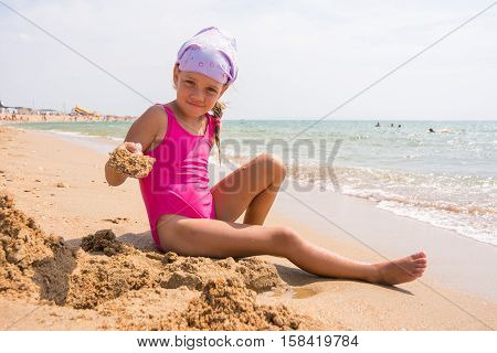 Girl Digs A Hole In The Sand On The Seashore