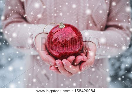 Female hands holding a Christmas red ball. Frosty winter day in snowy forest. Merry Christmas and Happy New Year theme